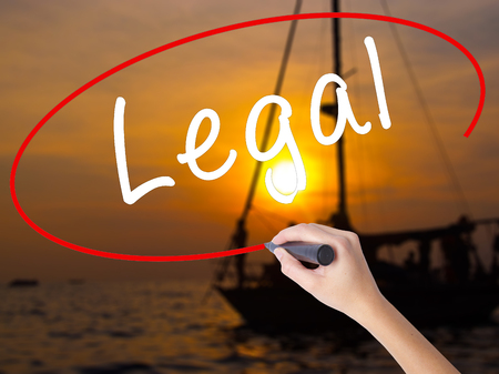 Woman Hand Writing Legal with a marker over transparent board. Isolated on Sunset Boat. Business, technology, internet concept. Stock Image