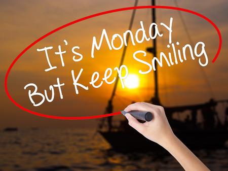 Woman Hand Writing Its Monday But Keep Smiling with a marker over transparent board. Isolated on Sunset Boat. Business, technology, internet concept. Stock Image