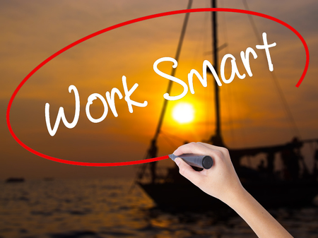 inteligent: Woman Hand Writing Work Smart with a marker over transparent board. Isolated on Sunset Boat. Business concept. Stock Photo