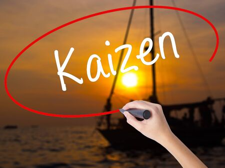 Woman Hand Writing Kaizen with a marker over transparent board. Isolated on Sunset Boat. Business concept. Stock Photo Stock Photo