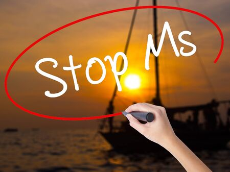 spasms: Woman Hand Writing Stop Ms with a marker over transparent board. Isolated on Sunset Boat. Business concept. Stock Photo