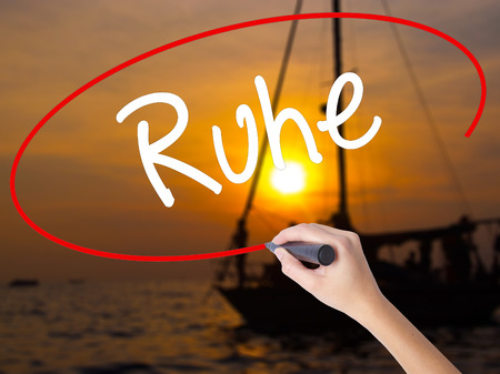repose: Woman Hand Writing Ruhe (Quiet in German) with a marker over transparent board. Isolated on Sunset Boat. Business concept. Stock Photo Stock Photo