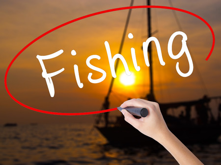 Woman Hand Writing Fishing with a marker over transparent board. Isolated on Sunset Boat. Business, technology, internet concept. Stock Image Stock Photo