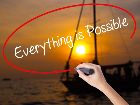 positivismo: Woman Hand Writing Everything is Possible with a marker over transparent board. Isolated on Sunset Boat. Business concept. Stock Photo