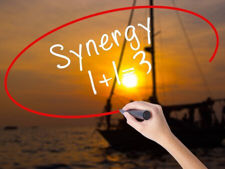 Woman Hand Writing Synergy concept 1+1=3 with a marker over transparent board. Isolated on Sunset Boat. Business, technology, internet concept. Stock Image Stock Photo