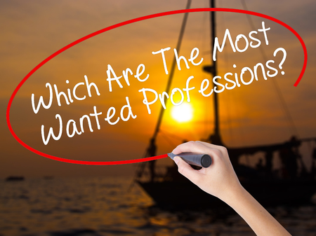 most talent: Woman Hand Writing Which Are The Most Wanted Professions? with a marker over transparent board. Isolated on Sunset Boat. Business concept. Stock Photo