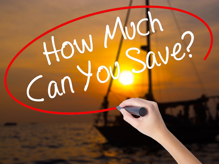 mortgaging: Woman Hand Writing How Much Can You Save? with a marker over transparent board. Isolated on Sunset Boat. Business concept. Stock Photo Stock Photo