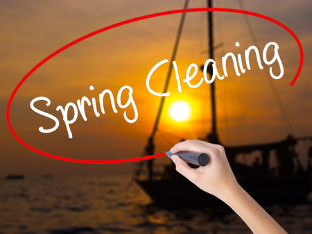 Woman Hand Writing Spring Cleaning with a marker over transparent board. Isolated on Sunset Boat. Business concept. Stock Photo