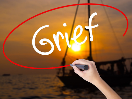Woman Hand Writing Grief with a marker over transparent board. Isolated on Sunset Boat. Business concept. Stock Photo Stock Photo