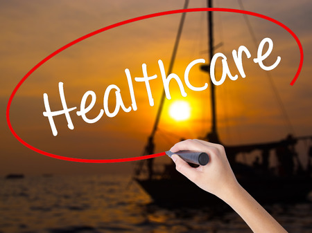 mandated: Woman Hand Writing Healthcare with a marker over transparent board. Isolated on Sunset Boat. Business concept. Stock Photo