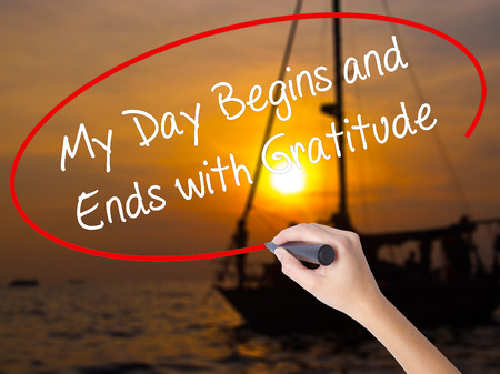 begins: Woman Hand Writing My Day Begins and Ends with Gratitude with a marker over transparent board. Isolated on Sunset Boat. Business concept. Stock Photo