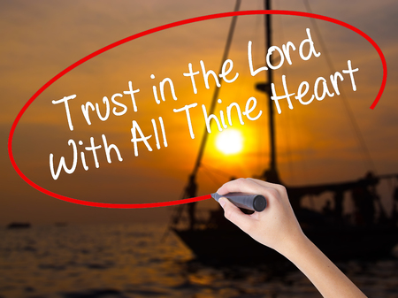 Woman Hand Writing Trust in the Lord With All Thine Heart with a marker over transparent board. Isolated on Sunset Boat. Business concept. Stock Photo Stock Photo