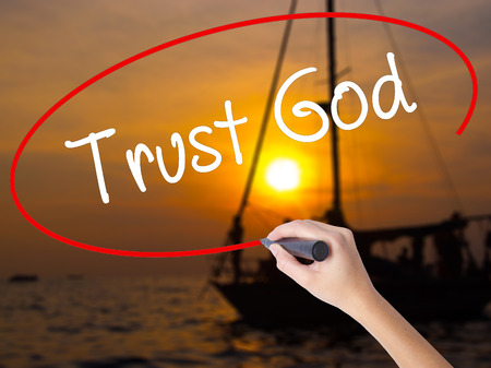 trust in god: Woman Hand Writing Trust God  with a marker over transparent board. Isolated on Sunset Boat. Business concept. Stock Photo