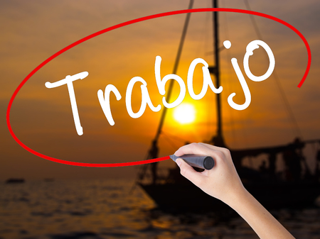 trabajo: Woman Hand Writing Trabajo  ( work in Spanish) with a marker over transparent board. Isolated on Sunset Boat. Business concept. Stock Photo
