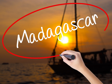 fort dauphin: Woman Hand Writing Madagascar with a marker over transparent board. Isolated on Sunset Boat. Business concept. Stock Photo Stock Photo