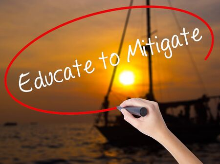 Woman Hand Writing Educate to Mitigate with a marker over transparent board. Isolated on Sunset Boat. Business concept. Stock Photo