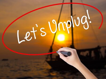 Woman Hand Writing Lets Unplug! with a marker over transparent board. Isolated on Sunset Boat. Business concept. Stock Photo