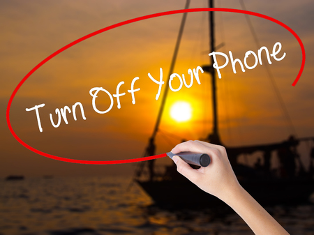 Woman Hand Writing Turn Off Your Phone with a marker over transparent board. Isolated on Sunset Boat. Business concept. Stock Photo