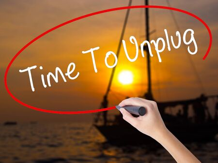 unplugging: Woman Hand Writing Time To Unplug with a marker over transparent board. Isolated on Sunset Boat. Business concept. Stock Photo Stock Photo