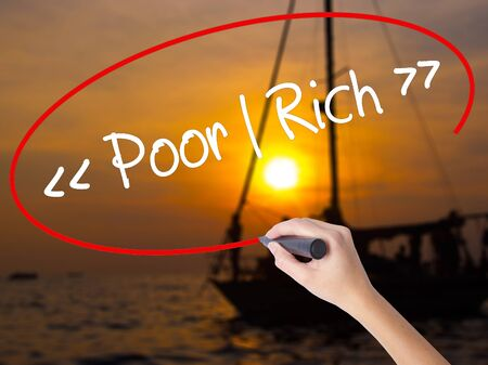 impoverished: Woman Hand Writing Poor - Rich with a marker over transparent board. Isolated on Sunset Boat. Business concept. Stock Photo Stock Photo