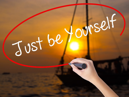 true self: Woman Hand Writing Just be Yourself with a marker over transparent board. Isolated on Sunset Boat. Business concept. Stock Photo