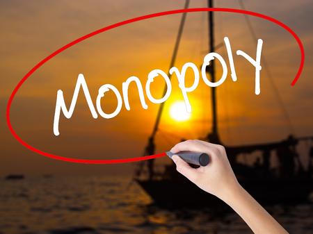 monopoly: Escritura de la mano de la mujer Monopoly con un marcador sobre un tablero transparente. Aislado en la puesta del sol del barco. Concepto de negocio. Foto de stock