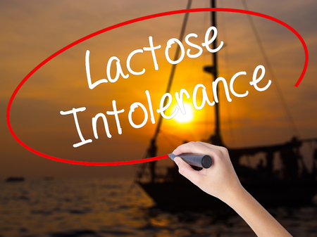 intolerancia: Woman Hand Writing Lactose Intolerance with a marker over transparent board. Isolated on Sunset Boat. Business concept. Stock Photo Foto de archivo