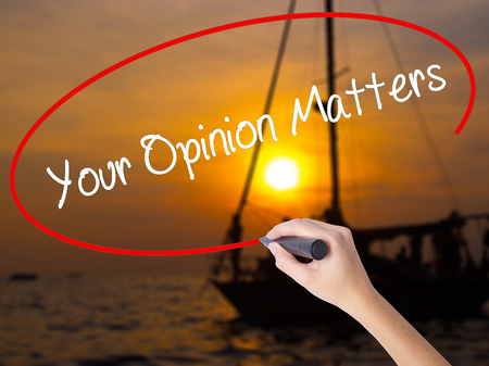 Woman Hand Writing Your Opinion Matters with a marker over transparent board. Isolated on Sunset Boat. Business, technology, internet concept.