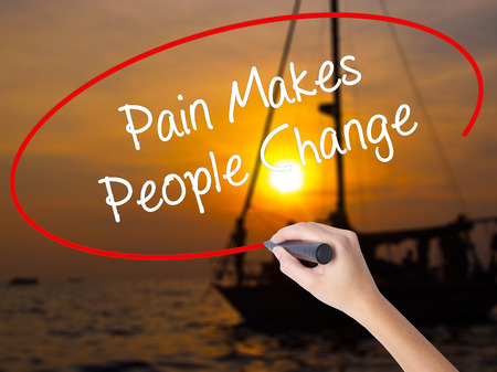 Woman Hand Writing Pain Makes People Change  with a marker over transparent board. Isolated on Sunset Boat. Business concept. Stock Photo Stock Photo