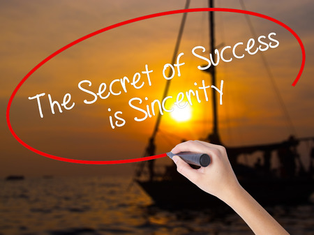 Woman Hand Writing The Secret of Success is Sincerity with a marker over transparent board. Isolated on Sunset Boat. Business concept. Stock Photo Stock Photo