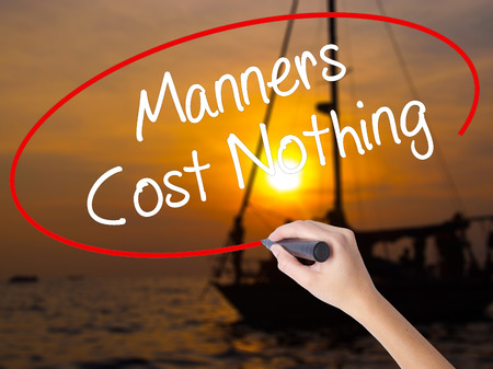 manners: Woman Hand Writing Manners Cost Nothing with a marker over transparent board. Isolated on Sunset Boat. Business concept. Stock Photo