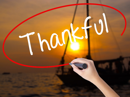 obliged: Woman Hand Writing Thankful  with a marker over transparent board. Isolated on Sunset Boat. Business concept. Stock Photo