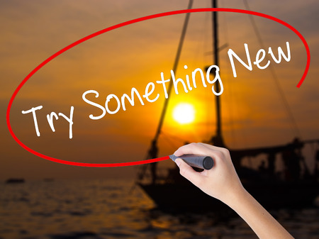 attempt: Woman Hand Writing Try Something New with a marker over transparent board. Isolated on Sunset Boat. Business concept. Stock Photo Stock Photo