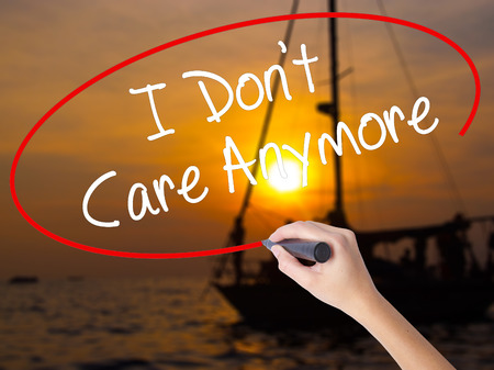 Woman Hand Writing I Dont Care Anymore with a marker over transparent board. Isolated on Sunset Boat. Business concept. Stock Photo
