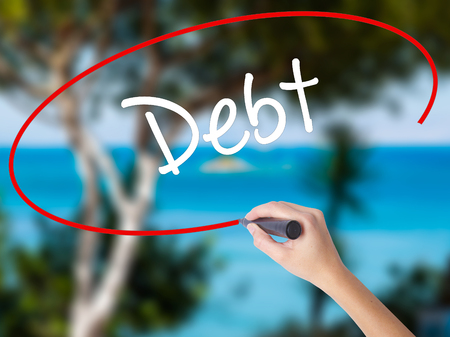 Woman Hand Writing Debt with black marker on visual screen. Isolated on nature. Business concept.
