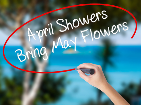 Woman Hand Writing April Showers Bring May Flowers with black marker on visual screen. Isolated on nature. Business concept. Stock Photo Stock Photo