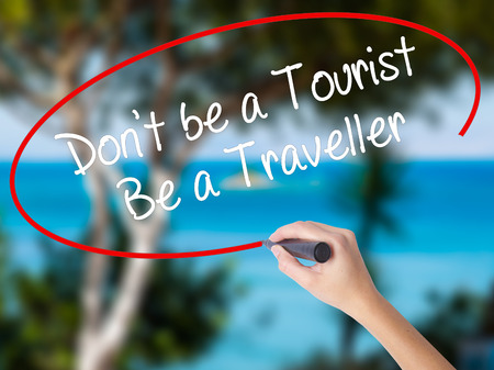 Woman Hand Writing Dont be a Tourist Be a Traveller  with black marker on visual screen. Isolated on nature. Business concept. Stock Photo Stock Photo