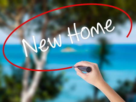 luxacion: Mano de la mujer que escribe nuevo hogar con el marcador negro en la pantalla visual. Aislado en la naturaleza. Concepto de negocio. Foto de stock