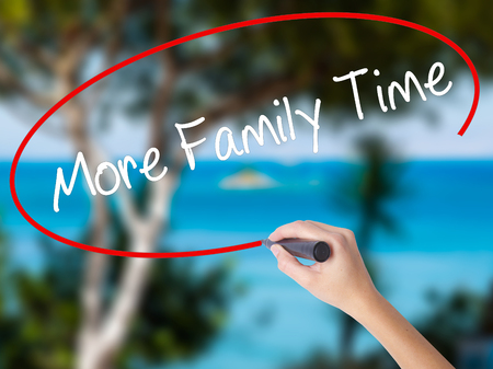 Woman Hand Writing More Family Time  with black marker on visual screen. Isolated on nature. Business concept. Stock Photo