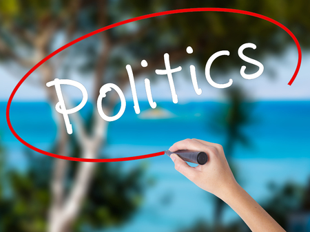 Woman Hand Writing Politics with black marker on visual screen. Isolated on nature. Business concept. Stock Photo Stock Photo