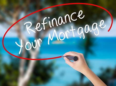 Woman Hand Writing Refinance Your Mortgage with black marker on visual screen. Isolated on nature. Business concept. Stock Photo Stock Photo