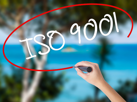 Woman Hand Writing  Iso 9001 with black marker on visual screen. Isolated on nature. Business concept. Stock Photo Stock Photo