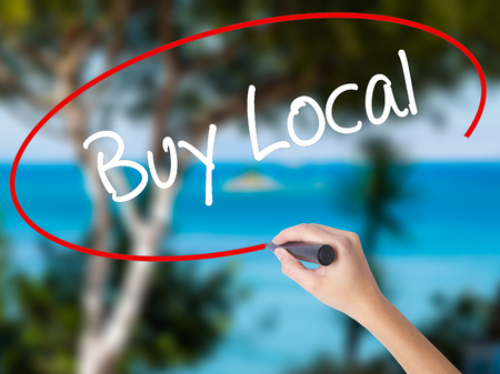 Woman Hand Writing Buy Local  with black marker on visual screen. Isolated on nature. Business concept. Stock Photo