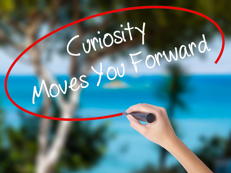 Woman Hand Writing Curiosity Moves You Forward with black marker on visual screen. Isolated on nature. Business concept. Stock Photo Stock Photo