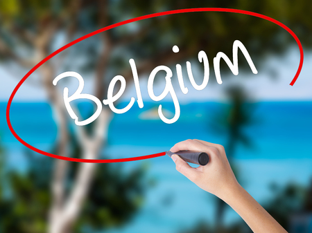 Woman Hand Writing Belgium  with black marker on visual screen. Isolated on nature. Business concept. Stock Photo