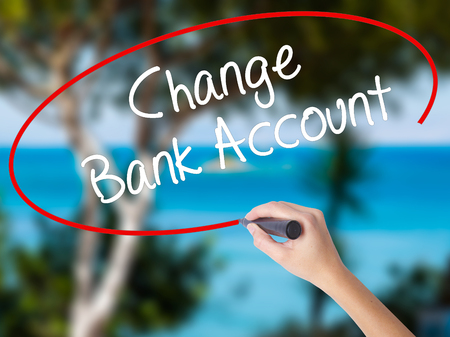 Woman Hand Writing Change Bank Account with black marker on visual screen. Isolated on nature. Business concept. Stock Photo