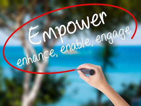 Escritura de la mano de la mujer Potenciar mejorar, habilitar, participar con marcador negro en la pantalla visual. Aislado en la naturaleza. Concepto de negocio. Foto de stock Foto de archivo