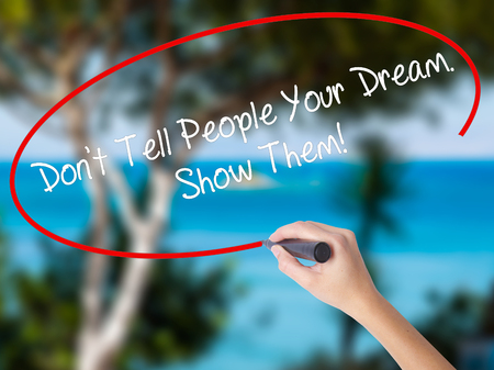 Woman Hand Writing Dont Tell People Your Dream. Show Them! with black marker on visual screen. Isolated on nature. Business concept.