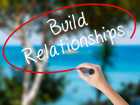 Woman Hand Writing Build Relationships with black marker on visual screen. Isolated on nature. Business concept. Stock Photo Stock Photo