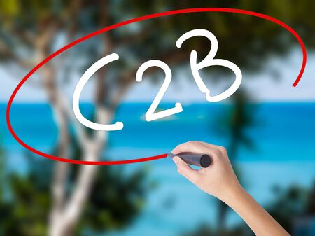 autoridad: Mujer mano escribiendo C2B con marcador negro en la pantalla visual. Aislado en la naturaleza. Concepto de negocio. Foto de stock Foto de archivo